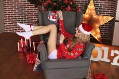 Muchacha hermosa en ropa y el sombrero caseros acogedores de Papá Noel que celebra el Ne Foto de archivo libre de regalías