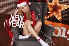 Muchacha hermosa en ropa y el sombrero caseros acogedores de Papá Noel que celebra el Ne Fotografía de archivo libre de regalías