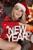 Muchacha hermosa en ropa y el sombrero caseros acogedores de Papá Noel que celebra el Ne Foto de archivo