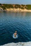 Muchacha hermosa en salto del acantilado en el mar Fotografía de archivo libre de regalías