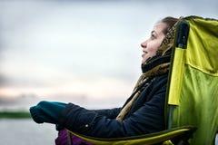 Muchacha hermosa en silla de la pesca que sonríe y que mira el cielo Imagenes de archivo