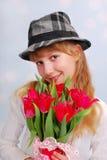 Muchacha hermosa en sombrero con los tulipanes Fotos de archivo