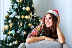 Muchacha hermosa en sombrero de la Navidad al lado del árbol de navidad Fotografía de archivo