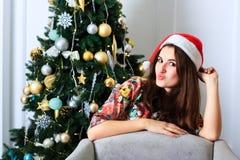 Muchacha hermosa en sombrero de la Navidad al lado del árbol de navidad Fotos de archivo libres de regalías