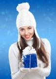 Muchacha hermosa en sombrero del invierno con un regalo. Imagen de archivo