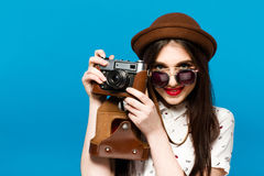 Muchacha hermosa en sombrero marrón y las gafas de sol redondas que sostienen la cámara vieja fotos de archivo libres de regalías