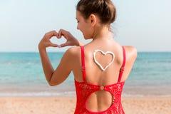 Muchacha hermosa en traje de ba?o rojo con la protecci?n solar en la forma del coraz?n en la parte posterior en la playa imagen de archivo