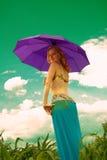 Muchacha hermosa en traje oriental con un umbrellain púrpura un campo Fotos de archivo libres de regalías