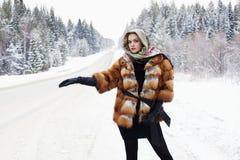 Muchacha hermosa en un abrigo de pieles que espera el coche en un camino del invierno en el bosque Imágenes de archivo libres de regalías