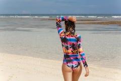 Muchacha hermosa en un bañador que camina en la playa con la arena blanca imagen de archivo libre de regalías