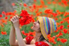 Muchacha hermosa en un campo con las amapolas Imágenes de archivo libres de regalías