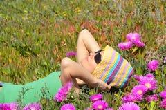 Muchacha hermosa en un campo con las flores rosadas Foto de archivo