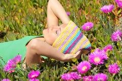 Muchacha hermosa en un campo con las flores rosadas Fotografía de archivo libre de regalías
