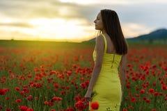 Muchacha hermosa en un campo de la amapola en la puesta del sol Foto de archivo libre de regalías