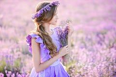 Muchacha hermosa en un campo de la lavanda en puesta del sol imágenes de archivo libres de regalías