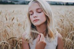 Muchacha hermosa en un campo de trigo Imagen de archivo libre de regalías