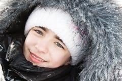 Muchacha hermosa en un capo motor de la piel en nieve. Foto de archivo