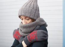 Muchacha hermosa en un casquillo hecho punto y las manoplas que congelan en el invierno o Fotos de archivo