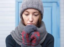 Muchacha hermosa en un casquillo hecho punto y las manoplas que congelan en invierno Imagenes de archivo
