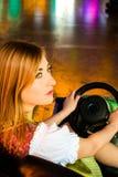 Muchacha hermosa en un coche de parachoques eléctrico adentro Fotografía de archivo libre de regalías