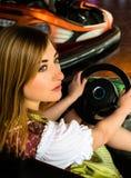 Muchacha hermosa en un coche de parachoques eléctrico adentro Foto de archivo libre de regalías