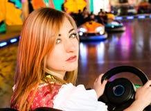 Muchacha hermosa en un coche de parachoques eléctrico en Fotografía de archivo libre de regalías