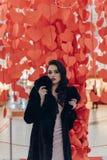 Muchacha hermosa en un fondo de corazones rojos Fotos de archivo