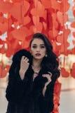Muchacha hermosa en un fondo de corazones rojos Foto de archivo libre de regalías