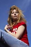 Muchacha hermosa en un fondo del cielo azul Imagen de archivo libre de regalías