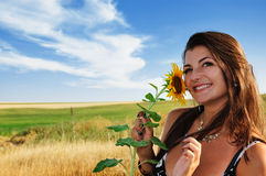 Muchacha hermosa en un girasol de la explotación agrícola del campo Fotografía de archivo