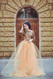 Muchacha hermosa en un oro, vestido lujoso imágenes de archivo libres de regalías