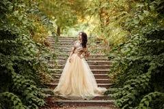 Muchacha hermosa en un oro, vestido lujoso imagenes de archivo