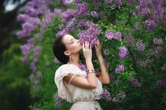 Muchacha hermosa en un parque con el árbol de las flores imagen de archivo libre de regalías