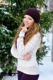 Muchacha hermosa en un sombrero del invierno y una bufanda y un punto hechos punto púrpura Fotos de archivo libres de regalías