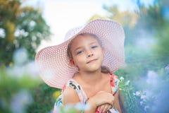 Muchacha hermosa en un sombrero rosado en verano en un jardín entre las flores imagenes de archivo