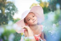 Muchacha hermosa en un sombrero rosado en verano en un jardín entre las flores fotografía de archivo