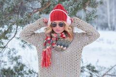 Muchacha hermosa en un sombrero y un suéter rojos en la nieve en rosa con los auriculares y la bufanda Fotos de archivo libres de regalías