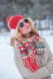 Muchacha hermosa en un sombrero y un suéter rojos en la nieve en rosa con los auriculares y la bufanda Foto de archivo