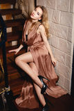 Muchacha hermosa en un vestido atractivo del oro foto de archivo