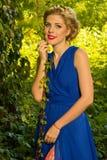 Muchacha hermosa en un vestido azul que presenta en bosque Imagenes de archivo