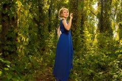 Muchacha hermosa en un vestido azul que presenta en bosque Fotos de archivo libres de regalías