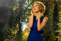 Muchacha hermosa en un vestido azul que presenta en bosque Foto de archivo libre de regalías