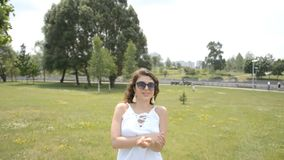Muchacha hermosa en un vestido blanco del verano y paseos del pelo rizado en un parque del verano metrajes