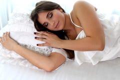 Muchacha hermosa en un vestido blanco que duerme en cama estudio imagen de archivo