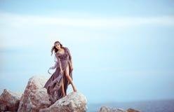 Muchacha hermosa en un vestido largo púrpura de hadas en piedras Foto de archivo libre de regalías