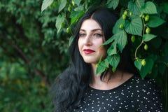 604b44dcf0 Muchacha hermosa en un vestido negro cerca de una casa verde vieja fotos de  archivo libres