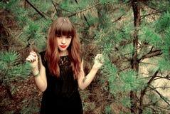 Muchacha hermosa en un vestido negro en un fondo del pino Imágenes de archivo libres de regalías
