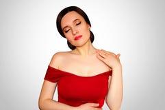 Muchacha hermosa en un vestido rojo con los hombros desnudos y lápiz labial rojo en un concepto gris claro del fondo de joyería d Foto de archivo