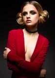 Muchacha hermosa en un vestido rojo con un escote profundo y anillos negros en sus fingeres El modelo con maquillaje brillante Imagen de archivo libre de regalías