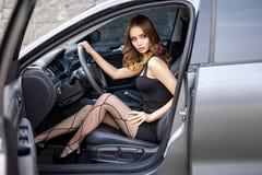 Muchacha hermosa en un vestido sexy en un coche moderno fotografía de archivo